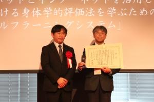 授賞式写真(梅村研文部科学省生涯学習政策局情報教育課長と徳永)